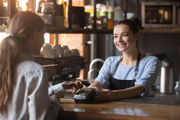 Female customer pay with phone on nfc with smiling barista