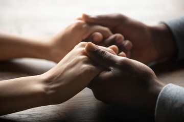 Mixed ethnicity couple holding hands on table, close up view