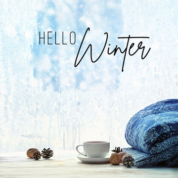 hello winter. Cup of tea and sweater on background of winter frost window. sweater weather, cozy home, winter holiday season background. shallow depth, soft selective focus