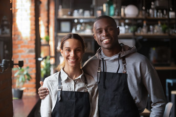 Happy diverse waiter and waitress looking at camera in restaurant Wall mural