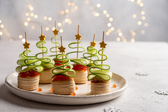 Christmas tree canape with cucumber slice, salmon pate and red caviar for festive xmas snack
