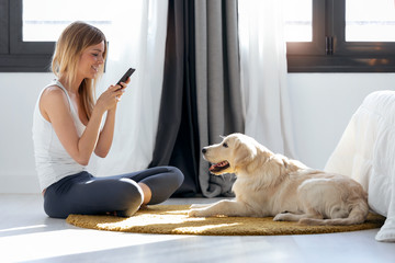 Pretty young woman taking photographs to her dog while staying on the floor at home.