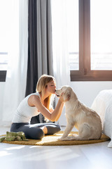 Pretty young woman kissing her dog while sitting on the floor at home.