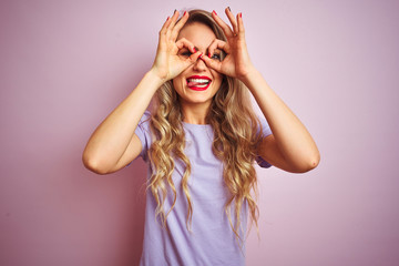 Young beautiful woman wearing purple t-shirt standing over pink isolated background doing ok...