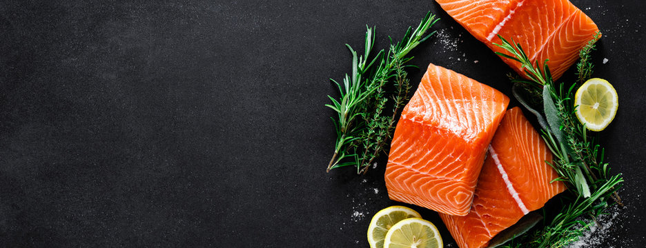 Salmon. Fresh raw salmon fish fillet with cooking ingredients, herbs and lemon on black background, top view, banner