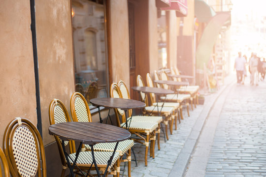 Empty tables in between dining hours. Old fashioned cafe terrace in a summer day