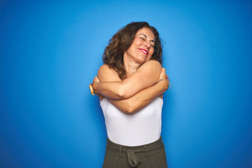 Wall Mural - Middle age senior woman with curly hair standing over blue isolated background Hugging oneself happy and positive, smiling confident. Self love and self care