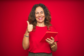 Middle age senior woman using touchpad tablet over red isolated background happy with big smile doing ok sign, thumb up with fingers, excellent sign