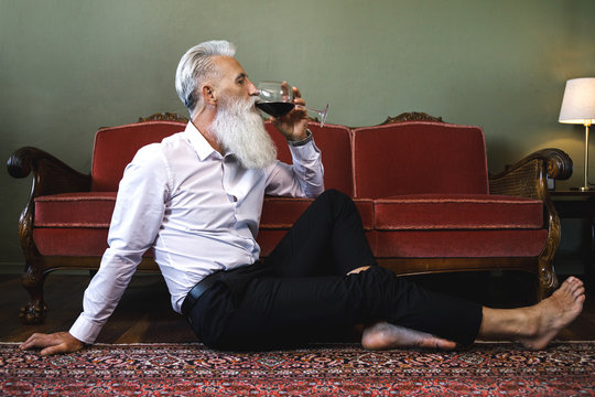 Handsome bearded senior man sitting on the floor and drinking red wine