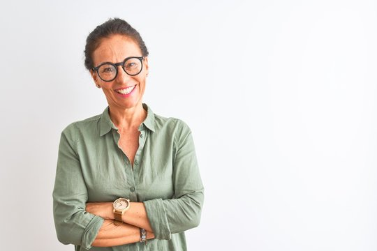 Middle age woman wearing green shirt and glasses standing over isolated white background happy face smiling with crossed arms looking at the camera. Positive person.