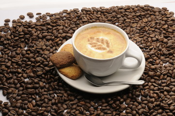 Taza de café con galletas y granos esparcidos