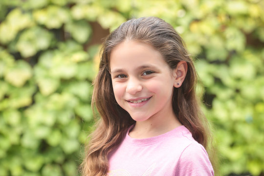 Close up Portrait of 8 Years Old Girl, with Brown Long Hair and Big Brown Eyes, Happy Child, Green Background