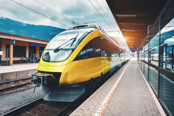 Beautiful high speed train on the railway station in mountains at sunset in autumn Yellow modern...