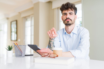 Young business man using touchpad tablet pointing with finger to the camera and to you, hand sign, positive and confident gesture from the front