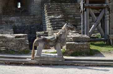 Wooden toy horse in the courtyard of a medieval fortress Fototapete
