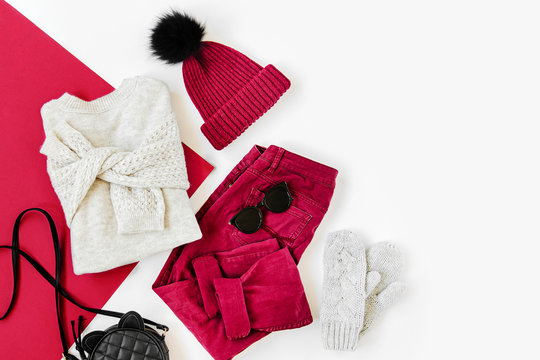 Vinous winter hat and trousers with sweater, handbag and mittens on white background. Women's stylish autumn or winter outfit. Trendy clothes collage. Flat lay, top view.