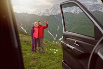 Happy couple making selfie by sell phone on beautiful mountains area out of car