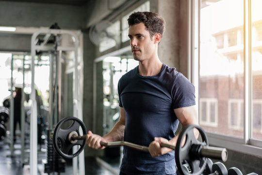 Handsome weightlifter lifting barbells working out with curl bar in the gym
