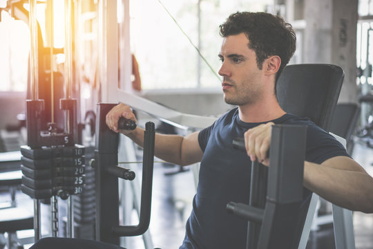 Handsome man lowering weight of fitness machine and working out in the fitness gym