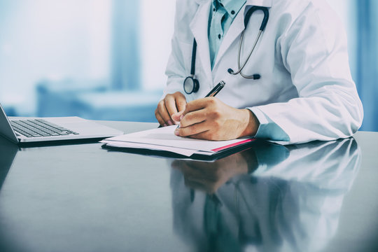 Male doctor sitting at table and writing on a document report in hospital office. Medical healthcare staff and doctor service.