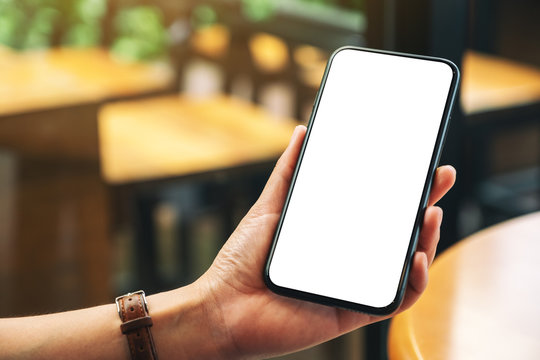 Mockup image of hands holding black mobile phone with blank desktop screen