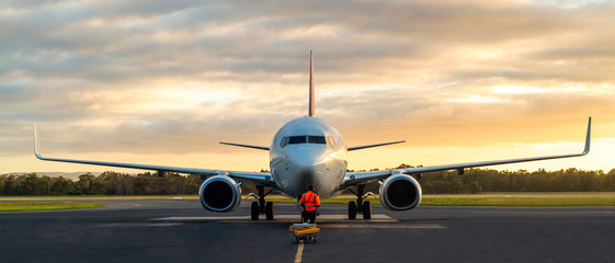 Sunset view of airplane on airport runway under dramatic sky in Hobart,Tasmania, Australia. Aviation technology and world travel concept. Fototapete