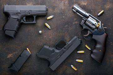 Gun with ammunition on iron dark background. Wall mural