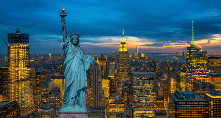 Fotomurales - The Statue of Liberty over the Scene of New York City cityscape in lower manhattan at the twilight time,Architecture and building with tourist concept, United state of America, USA