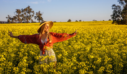 Laughing young lady with straw hat in yellow Canola Field in Western Australia Wall mural