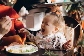 mother feeds her little baby from a spoon sitting on a highchair with a small table. Funny child with a smile eats what her mother gives her