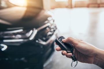 Hand presses unlock on the car remote control.