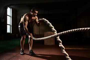 Muscular strong young man training with battle rope