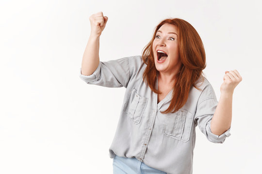 Supportive excited extremely happy lucky redhead middle-aged celebrating woman cheering son scored goal yelling yes triumphing clench raised fists joyfully victory gesture shout white background