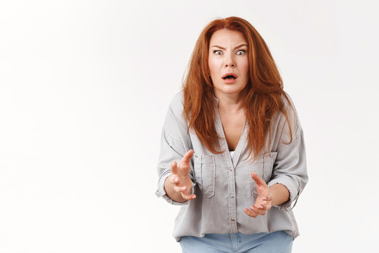 You did what. Shocked intense worried redhead disappointed middle-aged woman speechless stare camera gasping open mouth clench hands nervously facing large bee standing white background