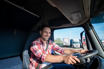 Shot of professional truck driver in casual clothing wearing seat belt on and driving his truck to destination. Smiling trucker enjoying his job. Transportation services. Fototapete