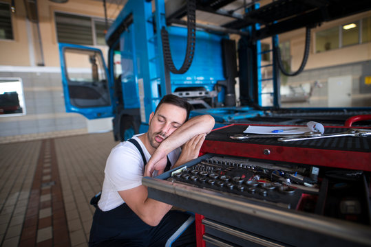 People sleeping at their job. Exhausted vehicle mechanic falling asleep in his workshop. Overworked and tired people.