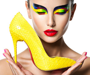 beautiful woman with vivid make-up of eyes holds the yellow high heel - fototapety na wymiar