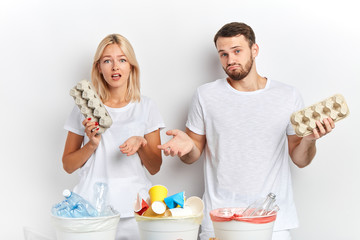 puzzled man and woman hesitating how to reuse eggs pack. close up portrait, studio shot