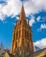 The church spire of St Paul's Cathedral in the city of Melbourne, Australia, set against a blue sky day.