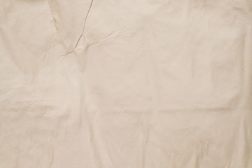 Beige colored wet paper. Creased texture. Moist surface effect. Abstract art background. Copy space.