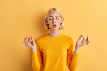 relaxed young woman meditating with eyes closed isolated over yelow background. lifestyle, free time, spare time