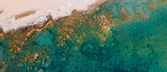 Image of sandy shore, rusty stones, azure sea.