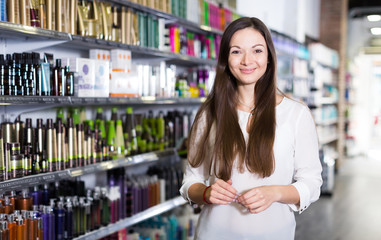 Young female customer standing in cosmetics studio