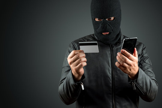 Robber, a thug in a balaclava holds a credit card in his hands on a dark background. Robbery, hacker, crime, theft. Copy space.