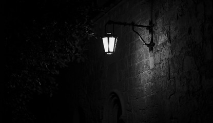 Spooky black and white alley with a lit street lamp Fotomurales