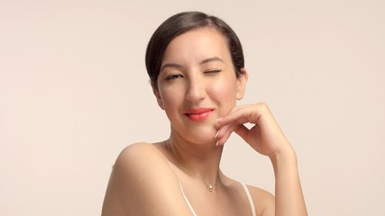 beauty brunette with short haircut model in studio alone with ideal shiny skin winks to camera