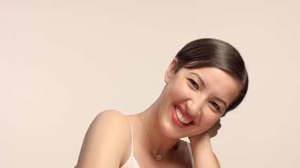 beauty brunette with short haircut model in studio alone with ideal shiny skin smiling to camera