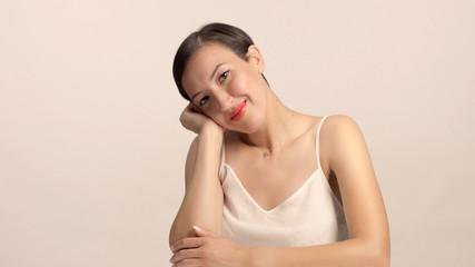 beauty brunette with short haircut model in studio alone with ideal shiny skin in position looks boed, but smiling