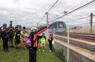 A protester throws a rock on the railroad tracks near Hong Kong International Airport
