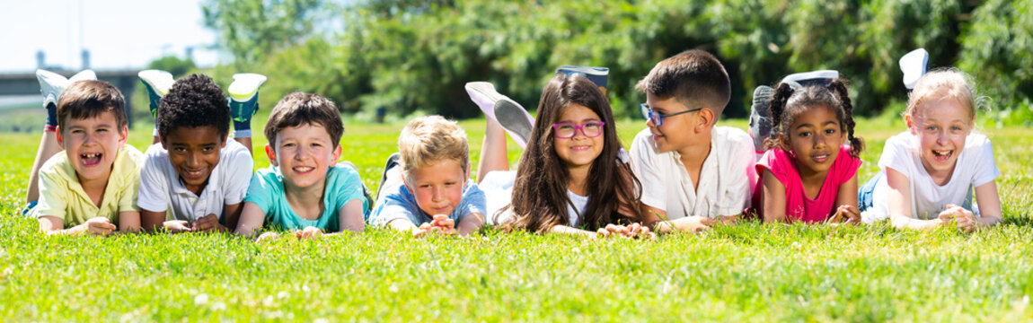 Team of friends children resting on grass together in park